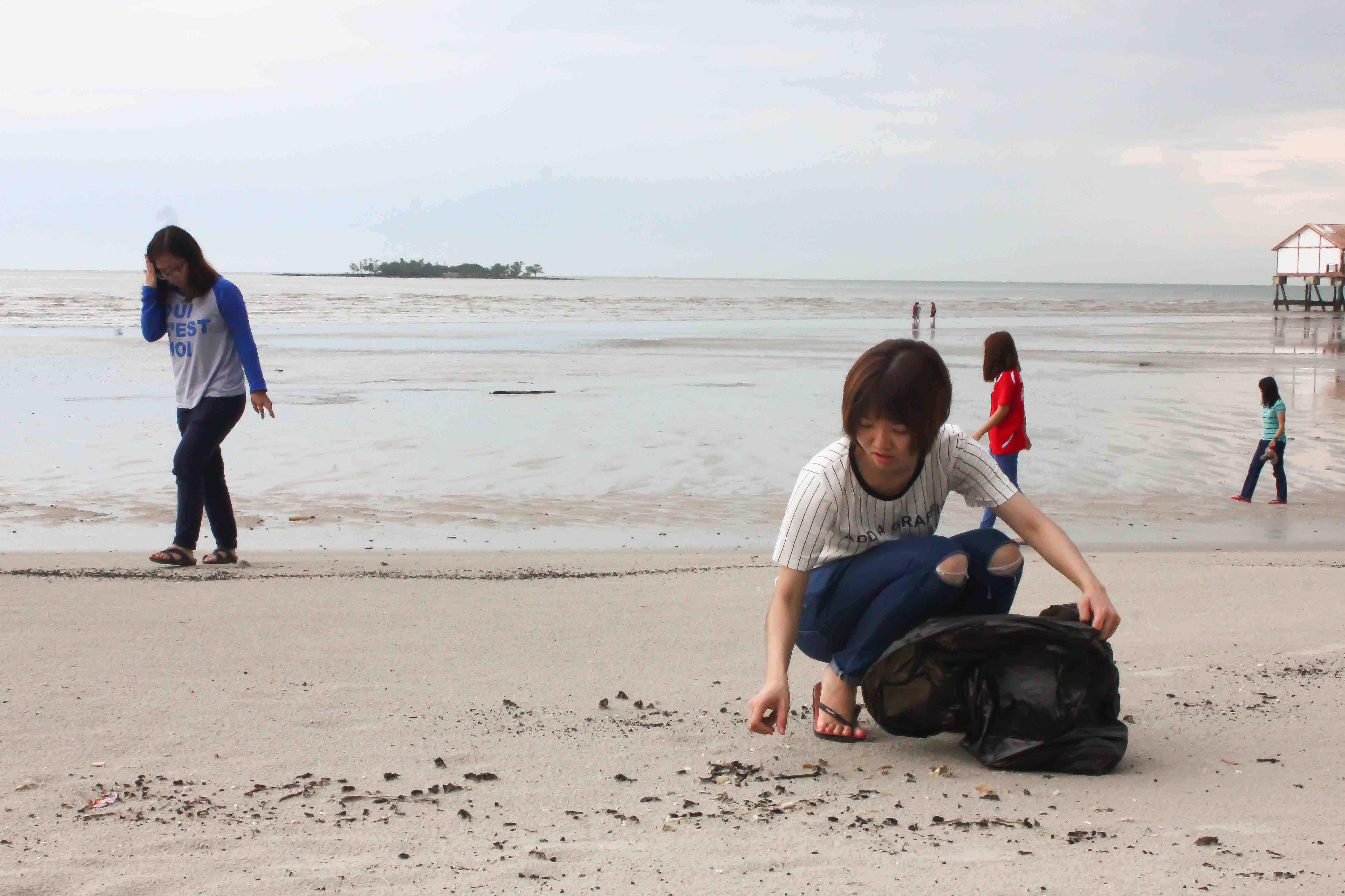 假日清理沙滩不偷懒 大学生用行动「说」我爱国家